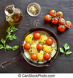 Gebratene Eier mit Tomaten in der Pfanne