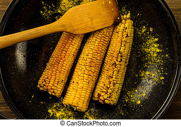 Gebratener Mais in einer Pfanne mit Gewürzen aus Holz. Gesundes vegetarisches Essen.