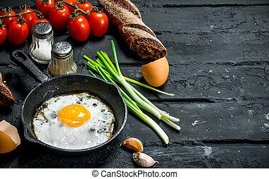 Gebratenes Ei in einer Pfanne mit Brot und Tomaten.