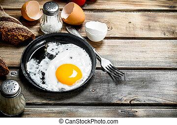 Gebratenes Ei in einer Pfanne mit Roggenbrot.