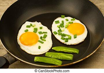 Gebratenes Ei mit Zwiebeln in einer Pfanne aus Holz.