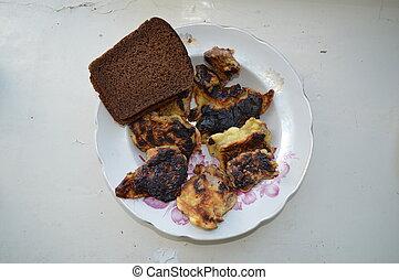 Gebratenes Fleisch in einer Pfanne mit Brot.