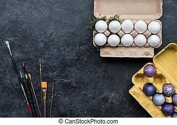 Gemalte und weiße Hühnereier in Kartons im dunklen Hintergrund.