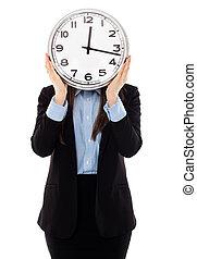 Geschäftsfrau deckt ihr Gesicht mit einer Uhr.