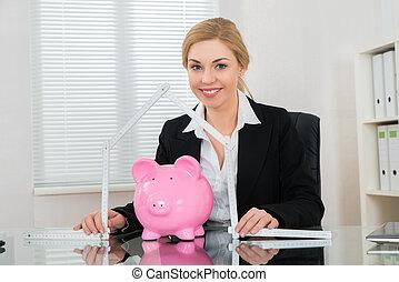 Geschäftsfrau mit Herrscherin gefaltet in Hausform und Sparschwein.