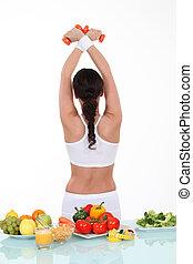 Gesundes Essen auf dem Tisch und sportliche Frau zurückgedreht.
