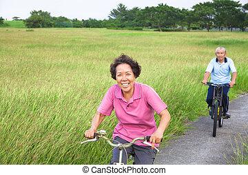 Glückliche Asiaten, ein paar Biker im Park.