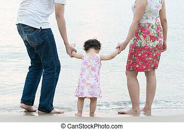 Glückliche asiatische Familie am Strand.