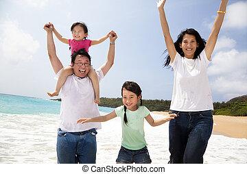 Glückliche asiatische Familie, die am Strand springt.