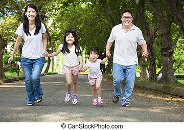 Glückliche asiatische Familie, die unterwegs ist