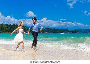 Glückliche Braut und Bräutigam haben Spaß an einem tropischen Strand.