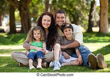 Glückliche Familie, die im Garten sitzt.