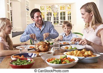 Glückliche Familie isst Brathähnchen am Tisch