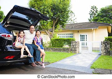 Glückliche Familie sitzt im Auto und ihr Haus dahinter