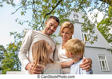 Glückliche Familie vor dem Haus draußen.