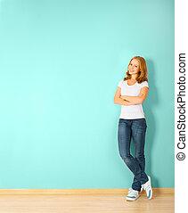 Glückliche Frau steht in einem Raum mit einer leeren Wand