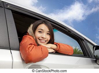 Glückliche junge Asiatin im Auto.