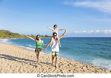 Glückliche junge Familie, die am Strand spazieren geht.