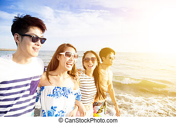 Glückliche junge Gruppe, die am Strand spazieren geht.