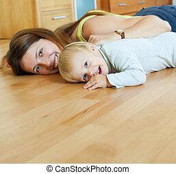 Glückliche Mutter und Kind auf Holzfußboden.