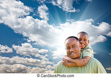 Glücklicher afroamerikanischer Mann mit Kind über Wolken und Himmel