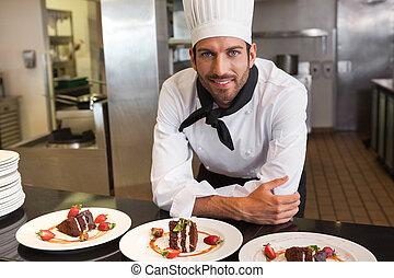 Glücklicher Koch, der die Kamera hinter dem Nachtisch sieht.