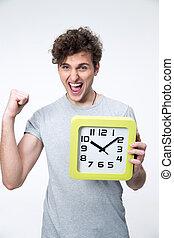 Glücklicher Mann, der die Uhr mit den Armen über grauem Hintergrund hält.