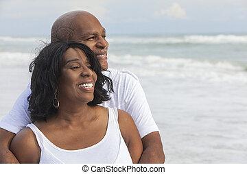 Glückliches afroamerikanisches Paar am Strand.