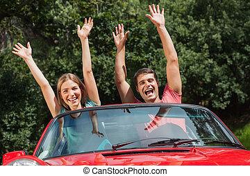 Glückliches Paar, das Spaß in seinem Cabriolet hat