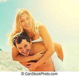 Glückliches Paar in der Liebe, umarmt und lacht am Strand.