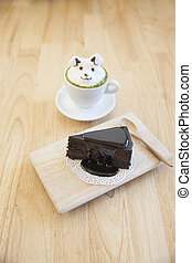 Grüner Tee mit Milchschaumtop auf der Tasse heißen grünen Tee und Schokoladenkuchen.