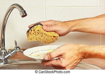 Hände mit schmutzigem Geschirr über dem Waschbecken in der Küche.
