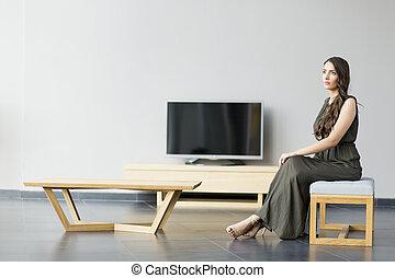 Hübsche junge Frau sitzt auf der Bank im modernen Zimmer.