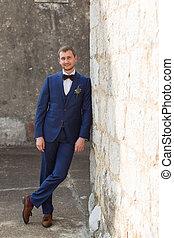 Hübscher Bräutigam in einem blauen Anzug.