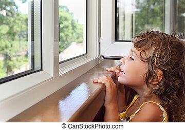 Hübsches lächelndes kleines Mädchen auf dem Balkon, schau aus dem Fenster