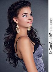 Haare. Schöne Frau mit langen schwarzen Haaren. Frisur. Wunderschönes Mädchenfoto. Ohrringe. Beihilfe