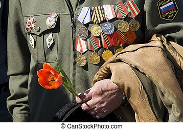Hand des Kriegsveteranen mit Tulpen
