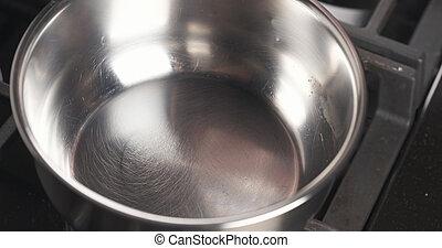 Handgestützte Spritze von Wasser in die Pfanne.