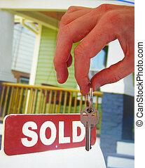Haus zum Verkauf mit verkauften Zeichen und Hand mit einem Schlüssel.
