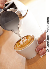 Heiße Milch, die in eine Tasse Kaffee gießt.