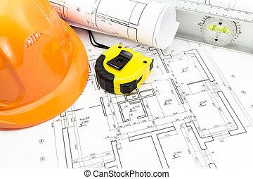 Helm, Blaupausen und Werkzeuge am Arbeitsplatz.