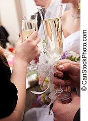 Hochzeitsbrille in Händen von Bräutigam und Braut