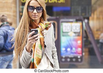 Junge, modische Frau mit Smartphone auf der Straße