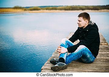 Junger, gutaussehender Mann, der auf dem Holzpier sitzt, sich entspannt, denkt: