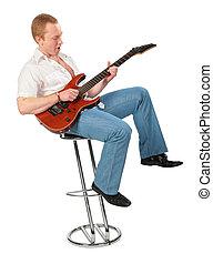 Junger Mann mit Gitarre auf dem Stuhl