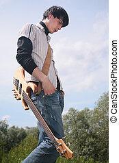 Junger Mann mit Gitarre im Gras