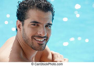 Junger Mann sitzt im Schwimmbad