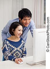 Junges asian Paar mit PC.