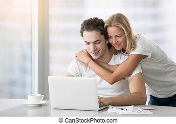 Junges glückliches Paar mit Laptop