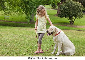 Junges Mädchen mit Hund im Park.